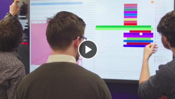 Two men studying a coloured chart on a large screen