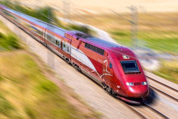 A Thalys high speed train at full speed in the countryside with motion blur.