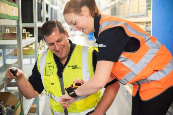 A woman in a Unipart Rail high visibility tabard speaking to a man on the apprenticeship programme in a warehouse.