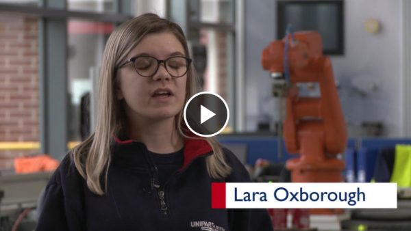 Woman in Unipart fleece being interviewed in a manufacturing facility