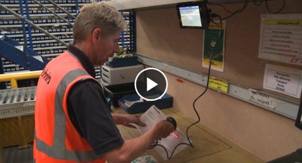 Man in orange hi-vis tabbard scanning an item in a warehouse