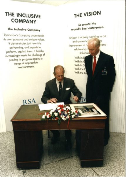 Prince Philip signs the visitors' book as John Neill looks on at Unipart in June 1995