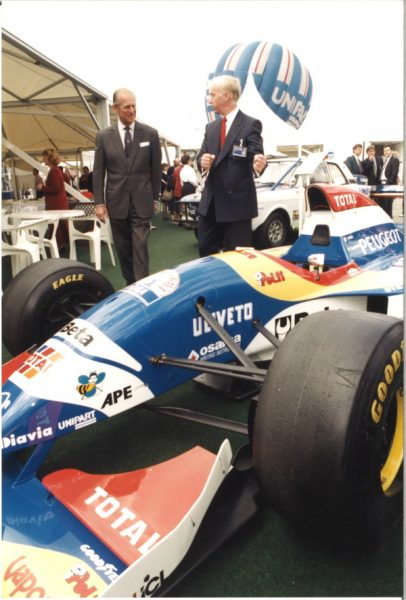 John Neill shows Prince Philip a Formula 1 car at Unipart in June 1995