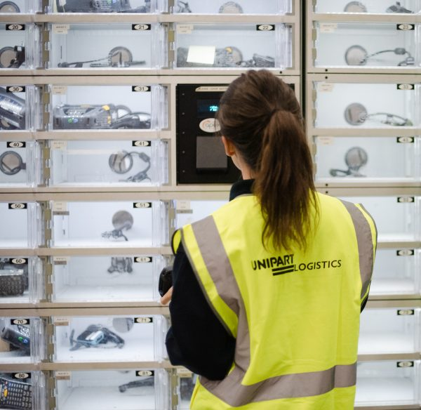 A woman in a Unipart Logistics safety tabard in front of lockers containing digital devices