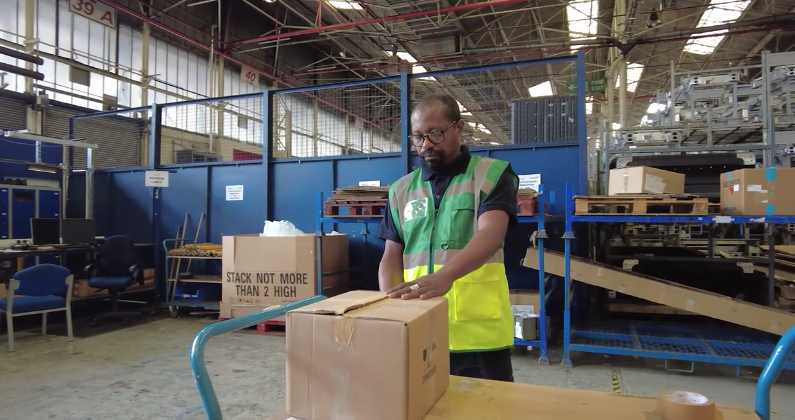 A Unipart employee recycling a box in a warehouse during Recycle Week